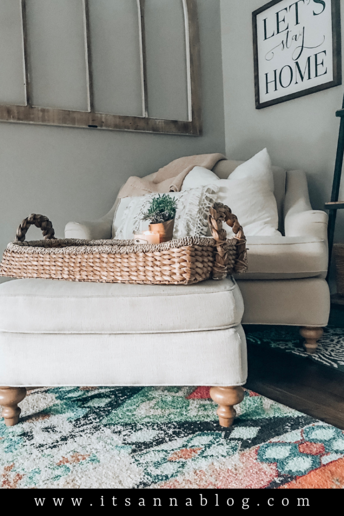 White chair and ottoman with a basket and lit candle.