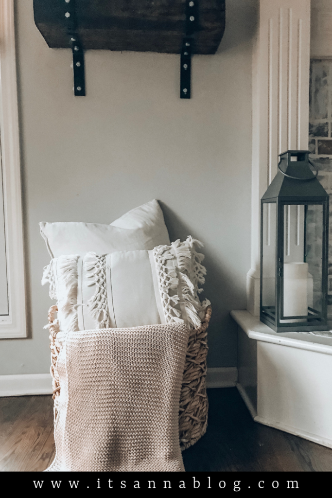 Wicker basket sitting on the floor next to fireplace with white pillows and a cozy throw blanket draped over the edge.